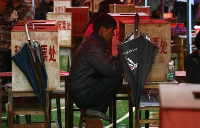 Un hombre, de cuclillas sobre un banco en China. (Reuters)