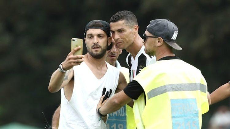Cristiano posó para la foto con el fanático que saltó al campo (Foto: AFP)