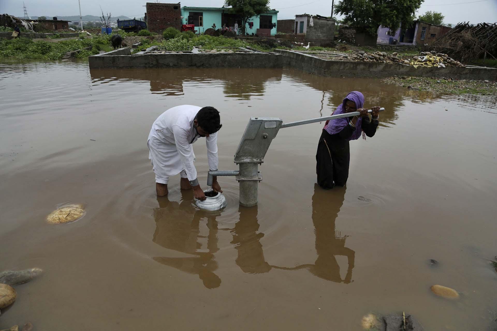 Una pareja recolecta agua potable en Jammu, India (AP Photo/Channi Anand)