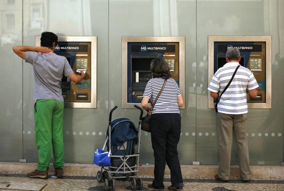Una madre con su bebé utiliza un cajero automático en el centro de Lisboa. (Reuters)