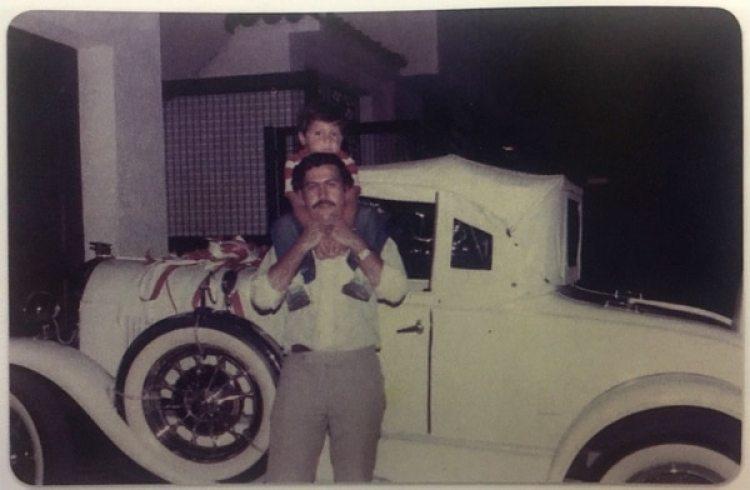 Juan Pablo sobre los hombros de Pablo Escobar, el día en que el jefe del Cartel de Medellín cumplió 30 años. Detrás, el automóvil que Victoria Henao le regaló para la ocasión (Victoria Eugenia Henao – Editorial Planeta)