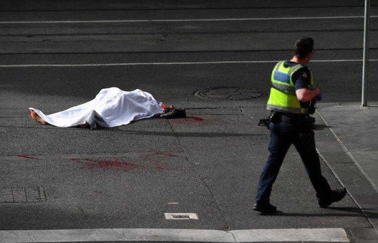 Un policía camina cerca del cuerpo de la víctima mortal del ataque (AAP/James Ross/via REUTERS)