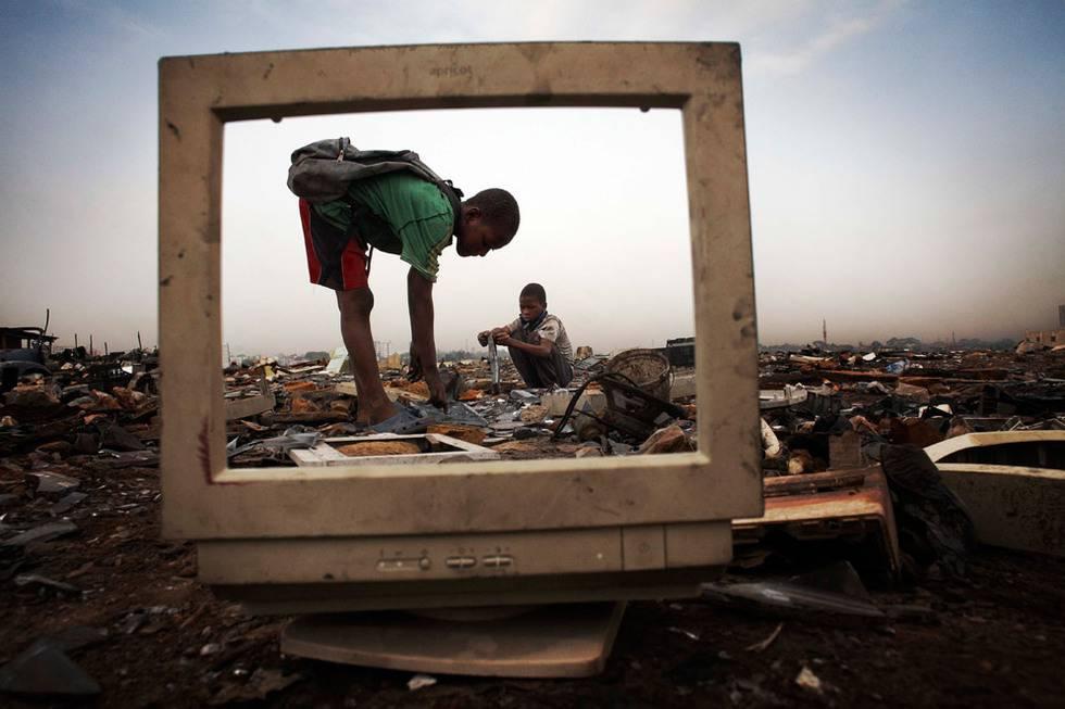 Unos niños recogen la parte metálica de una pantalla, en Agbogbloshie, barrio de Accra, Ghana. No se protegen para manipular productos químicos como el mercurio o el plomo. Fotografía de la serie fotográfica