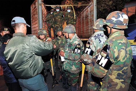Orden. Subteniente de Ejército imparte instrucciones a conscriptos de la Policía Militar fuera del cuartel.