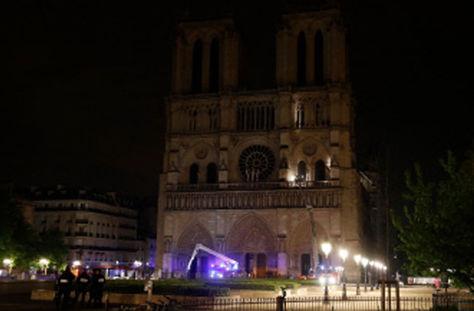 Los agentes de policía montan guardia mientras los bomberos trabajan frente a la Catedral de Notre-Dame en París.