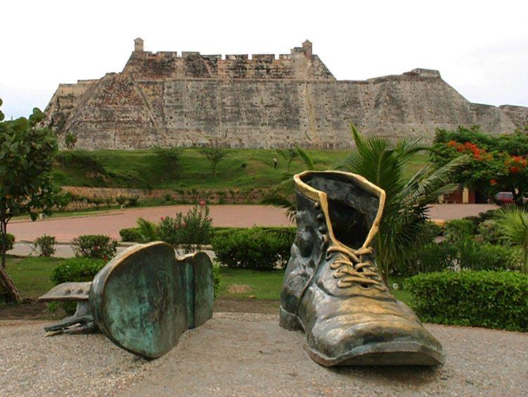 La obra los Zapatos Viejos con el Castillo de San Felipe de fondo. Esta obra es la réplica hecha por Héctor Lombana, hermano de Tito, que demolió la original por esta de bronce y se adjudicó su autoría.