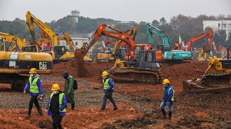 Los trabajadores caminan para dar paso a decenas de palas mecánicas y otras máquinas que construyen el hospital (Chinatopix vía AP)