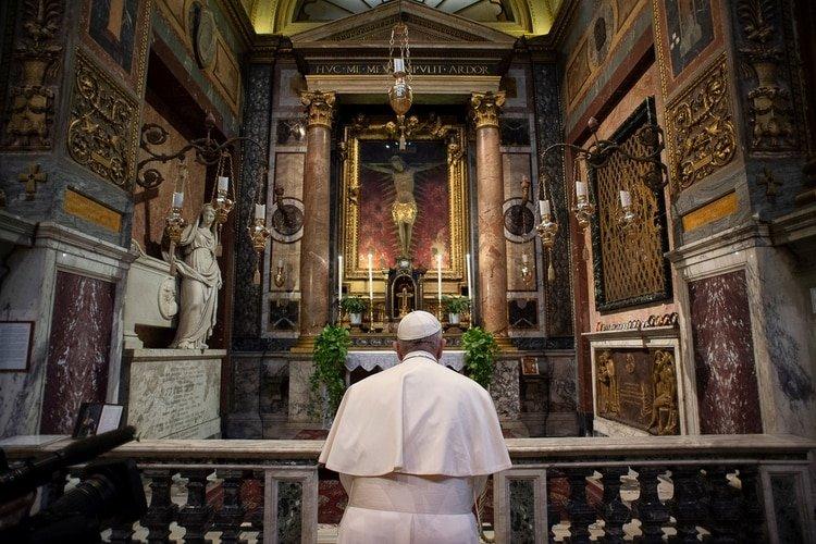 """El Papa Francisco reza frente al crucifijo que evoca la """"Gran Peste"""" de 1522 en la iglesia de San Marcello al Corso (Vatican Media via REUTERS)"""