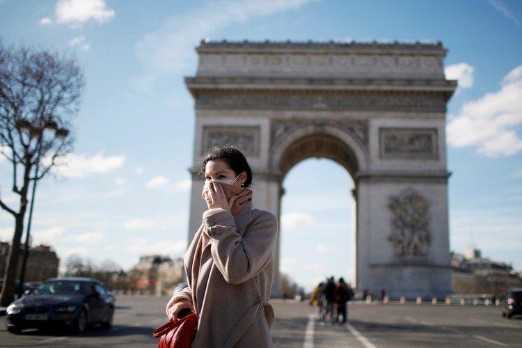 A woman wearing a protective mask, walks near Arc de Triomphe following France