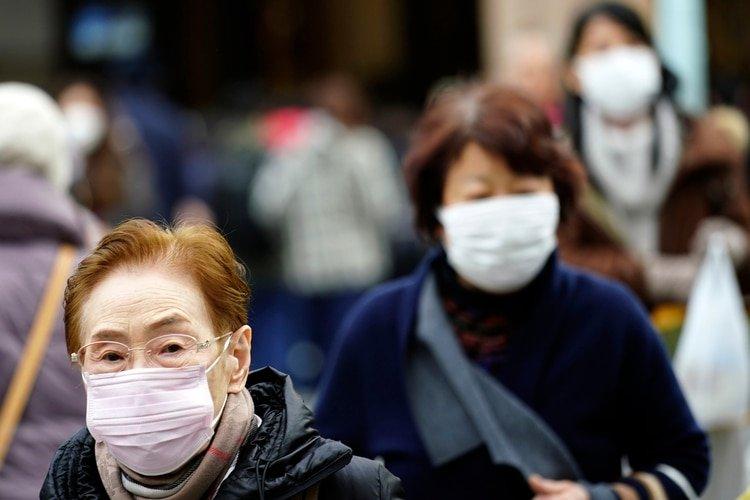 Peatones con mascarillas de protección en un distrito comercial de Tokio, el jueves 16 de enero de 2020. (AP Foto/Eugene Hoshiko)