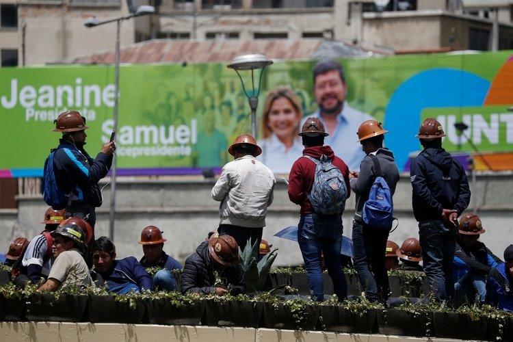 Mineros frente a un cartel de propaganda del binomio Jeanine Anez y Samuel Doria Medina en el centro de La Paz. La campaña está paralizada por la pandemia de coronavirus. (REUTERS/David Mercado)