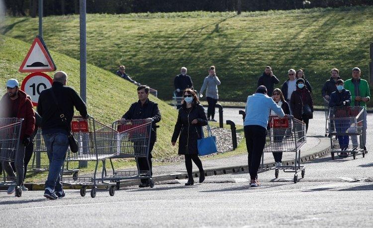 Una mujer usa una máscara facial protectora mientras las personas hacen cola fuera del supermercado Costco en Watford (Reuters)