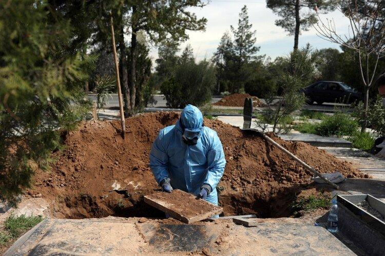 Un hombre iraní entierra al periodista Abdollah Zavieh, quien falleció debido a la enfermedad por coronavirus (COVID-19), en el cementerio Behesht Zahra en Teherán, Irán, 24 de marzo de 2020. (WANA/ Ali Khara vía REUTERS)