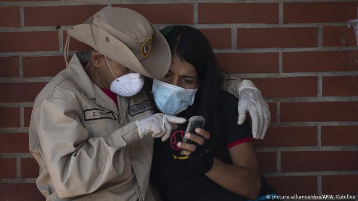 Venezuela | Coronavirus: Mitglied des Militärs und ein Anwohnerin mit Schutzmasken (picture-alliance/dpa/AP/A. Cubillos)