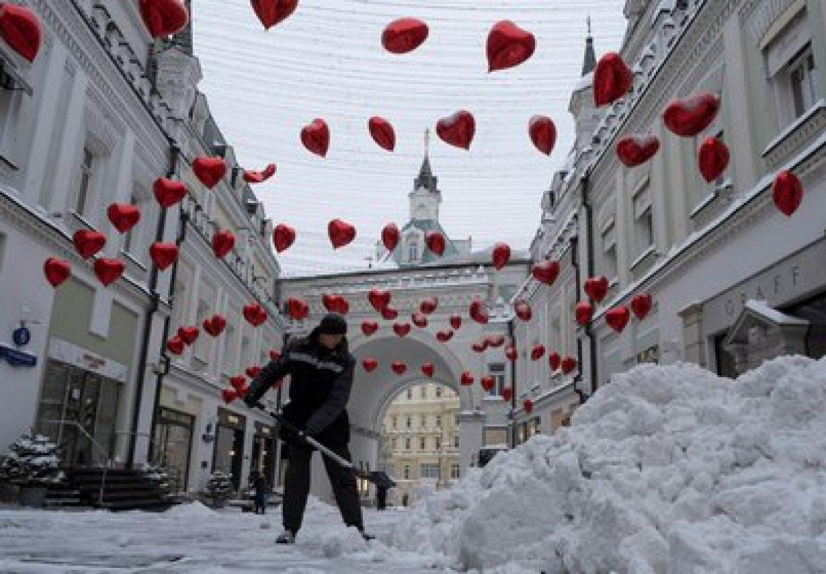 Un trabajador retira la nieve en una calle, que está decorada de cara al Día de San Valentín