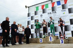 Ardigò is celebrating on the podium his victory in KZ, together with Camponeschi and Iglesias, the local authorities and the CIK-FIA Vice-President Kees van de Grint
