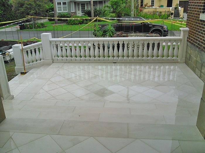 Masonry cast stone pavers and steps with a cast stone balustrade rail.