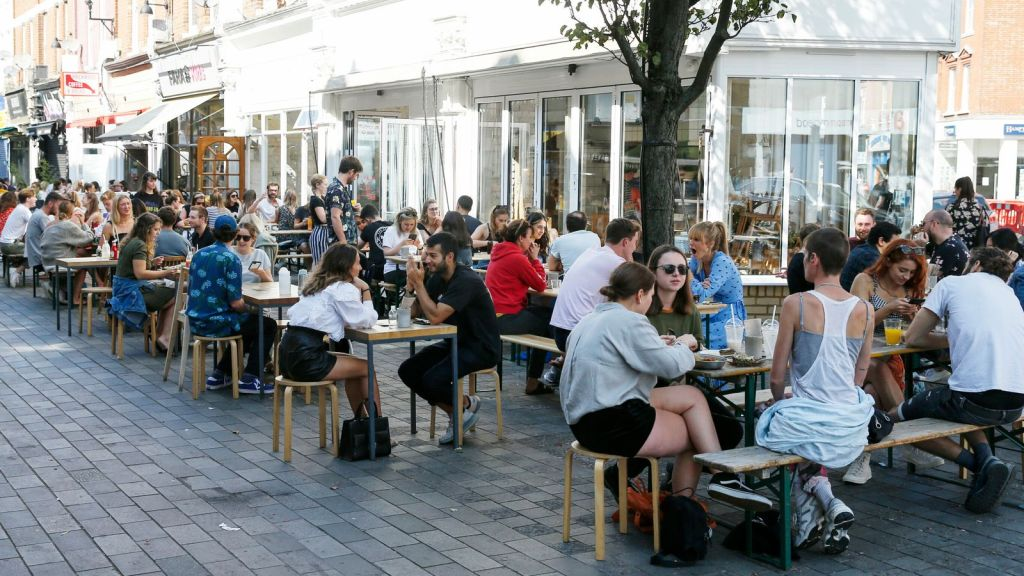 LONDON, ENGLAND - SEPTEMBER 13: People dine a restaurants and cafes in Balham on September 13, 2020 in London, England. Concerned by rising cases of Covid-19, the British government will start enforcing a six-person limit on indoor and outdoor social gatherings in England, although numerous exemptions exist for workplaces, schools, religious functions, and organised sport. (Photo by Hollie Adams/Getty Images)