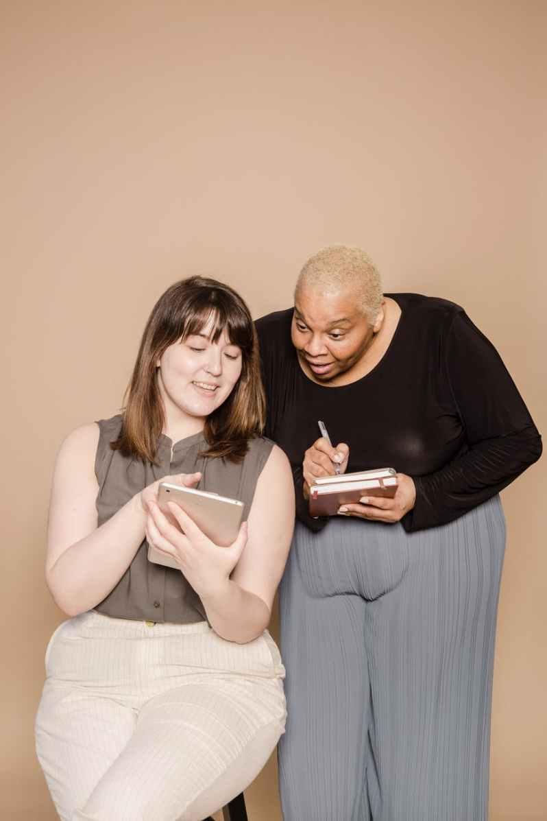 cheerful multiethnic plump women surfing tablet, körper als Feindbild