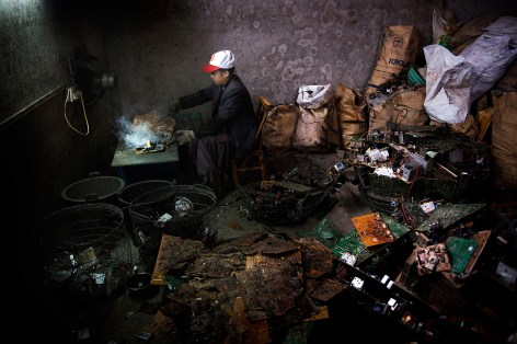 A man trying to salvage rare earth metals from e-waste in Guangdong district in China