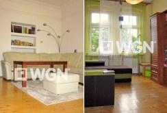 zdjęcie prezentuje po prawej fragment salonu, po lewej pokój w apartamencie do sprzedaży w Legnicy