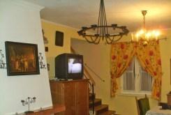 zdjęcie przedstawia fragment salonu z kominkiem w dworze na Mazurach do wynajmu