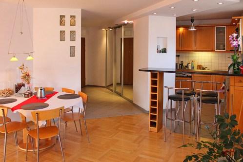 na zdjęciu widok z salonu na jadalnię oraz aneks kuchenny w apartamencie na sprzedaż w Warszawie