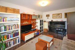 na zdjęciu fragment salonu z pianinem w apartamencie na sprzedaż w Łodzi