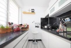 zdjęcie prezentuje urządzoną nowocześnie kuchnię w apartamencie do sprzedaży w Tarnowie