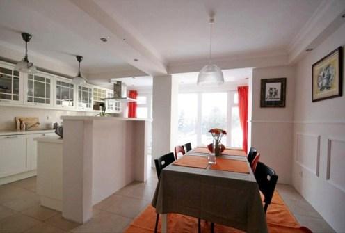 zdjęcie przedstawia jadalnię oraz aneks kuchenny na drugim planie w luksusowej willi do sprzedaży w Warszawie
