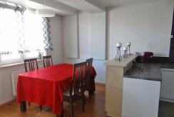 zdjęcie przedstawia jadalnię i fragment aneksu kuchennego w apartamencie do sprzedaży w okolicy Białegostoku