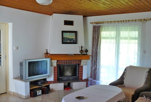 na zdjęciu wnętrze salonu z kominkiem w luksusowym dworze na sprzedaż w okolicy Suwałk