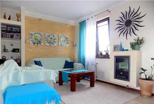 na zdjęciu salon z kominkiem w luksusowym apartamencie do sprzedaży w Ełku