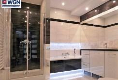 gustownie oświetlona, komfortowa łazienka w apartamencie do sprzedaży na Mazurach