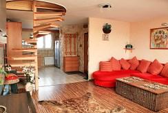 po lewej schody na górny poziom, po prawej salon w luksusowym apartamencie do sprzedaży w Szczecinie