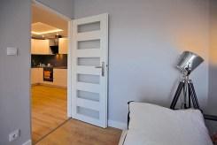 widok od strony sypialni na aneks kuchenny i salon w ekskluzywnym apartamencie w Szczecinie na wynajem