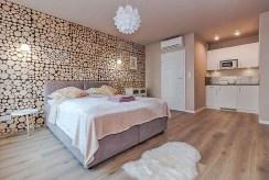 widok na sypialnię oraz aneks kuchenny w luksusowym apartamencie do sprzedaży w Krakowie
