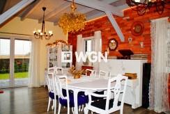 na pierwszym planie jadalnia, w oddali kuchnia w luksusowej willi do sprzedaży w okolicy Słupska