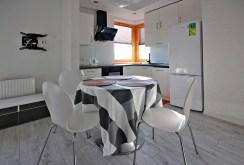 na pierwszym planie jadalnia, w oddali aneks kuchenny w ekskluzywnym apartamencie do wynajmu w Szczecinie