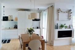 na pierwszym planie jadalnia, w oddali kuchnia w luksusowym apartamencie do sprzedaży Kraków