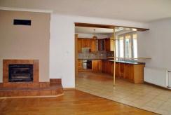salon z kominkiem i aneksem kuchennym w luksusowej willi do sprzedaży Słupsk (okolice)
