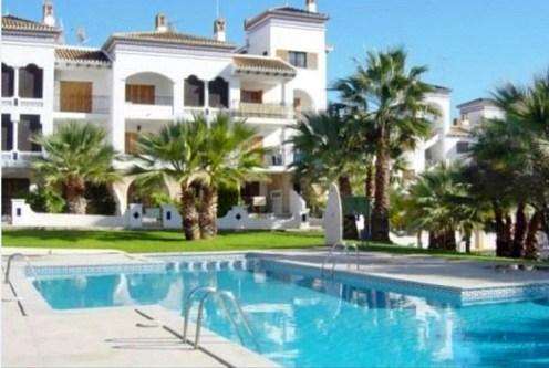 widok od strony basenu na apartamentowiec, w którym znajduje się oferowany na sprzedaż luksusowy apartament Hiszpania (Costa Blanca, Orihuela Costa)