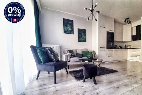 zaprojektowany zgodnie z najnowszymi trendami pokój dzienny, w oddali kuchnia w luksusowej willi na sprzedaż Leszno