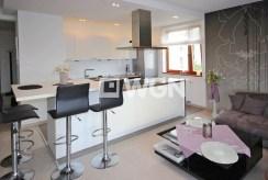 na pierwszym planie komfortowa kuchnia w luksusowym apartamencie do wynajmu Szczecin
