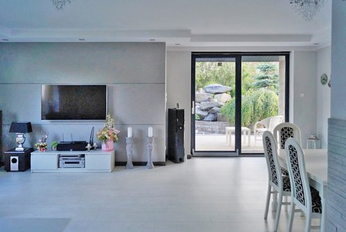 zdjęcie prezentuje pokój dzienny, aneks kuchenny i jadalnię w luksusowej willi na sprzedaż Konin (okolice)