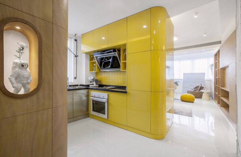 the-centrally-located-kitchen-volume-is-faced-with-high-gloss-lacquered-panels-and-features-a-yellow-tile-backsplash-with-black-artificial-stone-countertops