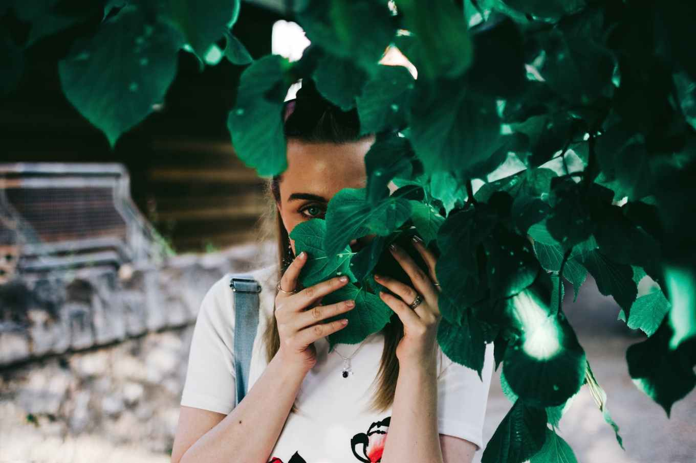 woman holding leaves covering her face