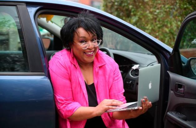 Donna, mamă a doi copii, lucrează din mașină