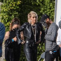 Miley Cyrus in an all-leather ensemble and she enjoys a large glass of red wine at a photoshoot