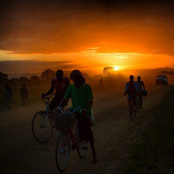 Ciclistas recorren una carretera mientras atardece en la zona rural de Ifkara, Tanzania. Foto: Nana Kofi Acquah / EverydayAfrica.